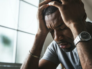 Black man looking overwhelmed with his head in his hands and in need of support